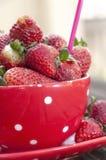 Κόκκινο φλυτζάνι με τις φράουλες Στοκ Φωτογραφίες