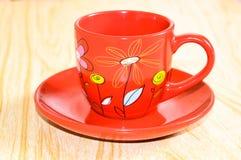 Κόκκινο φλυτζάνι σε ένα πιατάκι Στοκ Εικόνες