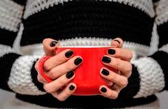 Κόκκινο φλυτζάνι του τσαγιού στα χέρια του Στοκ φωτογραφία με δικαίωμα ελεύθερης χρήσης