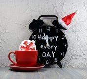 Κόκκινο φλυτζανιών καφέ με snowflake και ένα μαύρο ξυπνητήρι σε Χριστούγεννα ΚΑΠ με μια επιγραφή Στοκ Εικόνες