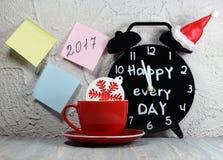 Κόκκινο φλυτζανιών καφέ με snowflake και τις αυτοκόλλητες ετικέττες και ένα μαύρο ξυπνητήρι σε Χριστούγεννα ΚΑΠ με μια επιγραφή Στοκ φωτογραφία με δικαίωμα ελεύθερης χρήσης