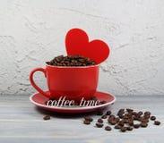 Κόκκινο φλυτζανιών με τα σιτάρια καφέ, την καρδιά και έναν χρόνο καφέ επιγραφής Στοκ φωτογραφίες με δικαίωμα ελεύθερης χρήσης