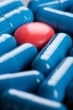 Κόκκινο χάπι μεταξύ των μπλε καψών Στοκ Φωτογραφίες
