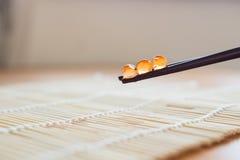 Κόκκινο χαβιάρι στα κινεζικά ραβδιά Στοκ Φωτογραφία