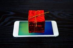 Κόκκινο χριστουγεννιάτικο δώρο στο τηλέφωνο Στοκ Φωτογραφίες