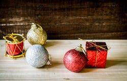 Κόκκινο χρυσό ασήμι μπιχλιμπιδιών Χριστουγέννων στον πίνακα Στοκ φωτογραφία με δικαίωμα ελεύθερης χρήσης
