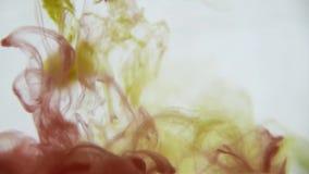 κόκκινο ύδωρ μελανιού κίτρ Το ζωηρόχρωμο κίτρινο και κόκκινο χρώμα ρίχνει άνωθεν να αναμίξει στο νερό, να στροβιλιστεί μαλακά υπο απόθεμα βίντεο