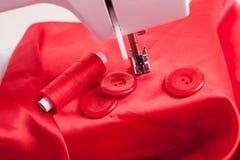 Κόκκινο ύφασμα και ράβοντας εξαρτήματα Στοκ εικόνα με δικαίωμα ελεύθερης χρήσης