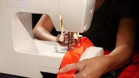 Κόκκινο ύφασμα που ράβει στη ράβοντας μηχανή κλείστε επάνω απόθεμα βίντεο
