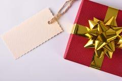 Κόκκινο δώρο με τη χρυσή κορδέλλα και ετικέτα στο αριστερό Στοκ Εικόνα