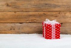 Κόκκινο δώρο Χριστουγέννων με το χιόνι Στοκ Φωτογραφία