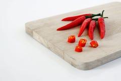 Κόκκινο Chilis στον τεμαχίζοντας πίνακα Στοκ Φωτογραφία