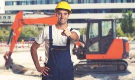 Κόκκινο earthmover με την υπόδειξη του λατινοαμερικάνικου εργάτη οικοδομών στοκ εικόνα