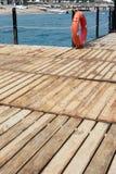 Κόκκινο Lifebuoy στην ξύλινη αποβάθρα Στοκ Εικόνες