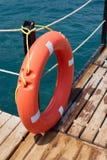 Κόκκινο Lifebuoy στην ξύλινη αποβάθρα Στοκ Φωτογραφίες