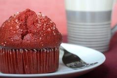 Κόκκινο muffin βελούδου σε ένα πιάτο που εξυπηρετείται με τον καφέ Στοκ Φωτογραφίες