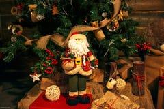 Κόκκινο santa κοντά στο πράσινο χριστουγεννιάτικο δέντρο Στοκ Φωτογραφίες