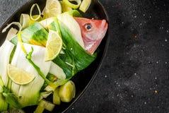 Κόκκινο tilapia ακατέργαστων ψαριών που τυλίγεται στο πράσο στοκ εικόνες με δικαίωμα ελεύθερης χρήσης