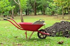 Κόκκινο wheelbarrow στον κήπο Στοκ Εικόνα
