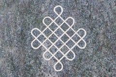Κόμβος που χαράσσεται ατελείωτος στην επιφάνεια πετρών Στοκ εικόνα με δικαίωμα ελεύθερης χρήσης
