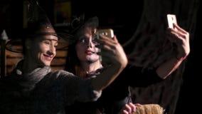Κόμμα αποκριών, νύχτα, γυναίκες στο λυκόφως, στις ακτίνες του φωτός γυναίκες με ένα φοβερό makeup στις μαύρες μάγισσες κοστουμιών απόθεμα βίντεο