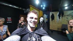 Κόμμα αποκριών, νύχτα, εκφοβίζοντας πορτρέτο ενός ατόμου με ένα φοβερό makeup σε ένα μαύρο κοστούμι μαγισσών, κοασμοί μπροστά από φιλμ μικρού μήκους