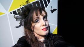 Κόμμα αποκριών, νύχτα, εκφοβίζοντας πορτρέτο μιας γυναίκας με ένα φοβερό makeup σε ένα μαύρο κοστούμι μαγισσών, κοασμοί μπροστά α απόθεμα βίντεο