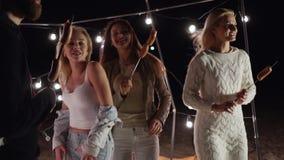 Κόμμα διασκέδασης νεολαίας στην παραλία νύχτας, άνθρωποι που χορεύει σε ένα υπόβαθρο του ντεκόρ με τους λαμπτήρες απόθεμα βίντεο