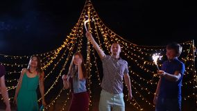 Κόμμα και φίλοι παραλιών νύχτας που χορεύουν με τα sparklers φιλμ μικρού μήκους