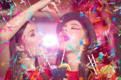 Κόμμα κομφετί Δύο λεσβίες νέων κοριτσιών σε ένα κόμμα στη λέσχη κρατούν τα κεράσια κοκτέιλ στοκ εικόνες
