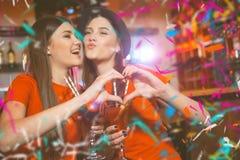Κόμμα κομφετί Δύο νέα λεσβιακά κορίτσια κάνουν μια καρδιά με τα χέρια τους σε ένα κόμμα λεσχών στοκ εικόνα