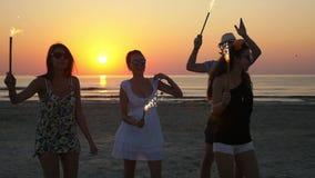 Κόμμα με τα πυροτεχνήματα στην παραλία στο ηλιοβασίλεμα απόθεμα βίντεο