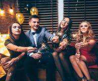 Κόμμα με τους φίλους Ευτυχείς νέοι που φέρνουν τα sparklers και το εκτάριο στοκ φωτογραφίες