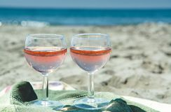 Κόμμα παραλιών με την άποψη θάλασσας, ρομαντικός εορτασμός σχετικά με την ηλιόλουστη αμμώδη παραλία, δύο γυαλιά με το ροδαλό κρασ στοκ εικόνες