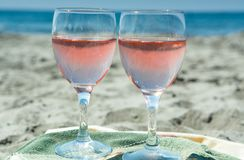 Κόμμα παραλιών με την άποψη θάλασσας, ρομαντικός εορτασμός σχετικά με την ηλιόλουστη αμμώδη παραλία, δύο γυαλιά με το ροδαλό κρασ στοκ φωτογραφία