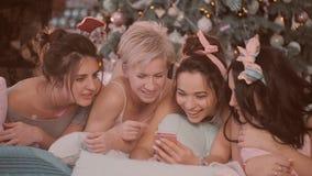Κόμμα πυτζαμών κορίτσια στις πυτζάμες που έχουν τη διασκέδαση κοντά σε ένα χριστουγεννιάτικο δέντρο απόθεμα βίντεο