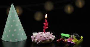 Κόμμα Ρόδινο doughnut και ένα κόκκινο εορταστικό κερί σε το Χρυσή πτώση κομφετί φιλμ μικρού μήκους