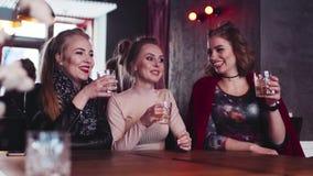 Κόμμα τριών πανέμορφο γυναικών σκληρό με τα κοκτέιλ οινοπνεύματος Έχοντας τη διασκέδαση με αληθινοί φίλοι, φρυγανιά κατανάλωσης σ φιλμ μικρού μήκους