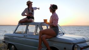 Κόμμα τσαγιού των φίλων στη μηχανή στη θάλασσα ακτών στο ηλιοβασίλεμα, καλές φίλες που πίνει τον καφέ φιλμ μικρού μήκους