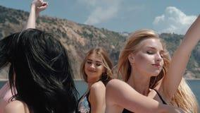 Κόμμα των νέων γυναικών στο μπικίνι στο γιοτ σε σε αργή κίνηση φιλμ μικρού μήκους