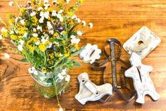 Κόπτες και λουλούδια μπισκότων κασσίτερου που κάθονται στον ξύλινο πίνακα στοκ φωτογραφία με δικαίωμα ελεύθερης χρήσης