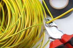 Κόπτες καλωδίων, με μια δέσμη των κιτρινοπράσινων καλωδίων και της ηλεκτρικής ταινίας στοκ φωτογραφία με δικαίωμα ελεύθερης χρήσης