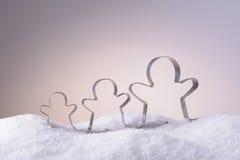 Κόπτες μπισκότων για τα μπισκότα Χριστουγέννων στο χιόνι Στοκ φωτογραφία με δικαίωμα ελεύθερης χρήσης