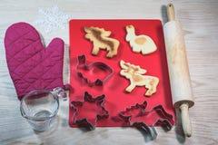 Κόπτες μπισκότων και σπιτικά μπισκότα στον ξύλινο πίνακα στοκ εικόνες