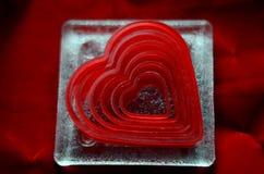 Κόπτες μπισκότων καρδιών στον ακτοφύλακα γυαλιού στο κόκκινο κλίμα βελούδου Στοκ φωτογραφία με δικαίωμα ελεύθερης χρήσης