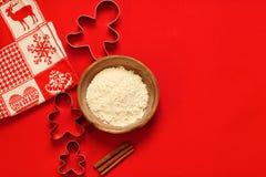 Κόπτες μπισκότων σύνθεσης Χριστουγέννων και ένα κύπελλο του αλευριού στο κόκκινο υπόβαθρο στοκ φωτογραφίες