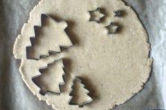 Κόπτες μπισκότων Χριστουγέννων στην ακατέργαστη ζύμη στη τοπ άποψη περγαμηνής Στοκ Φωτογραφίες