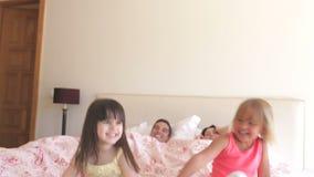 Κόρες που πηδούν στο κρεβάτι γονέων απόθεμα βίντεο