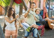 Κόρες στην ταλάντευση με τους γονείς Στοκ φωτογραφία με δικαίωμα ελεύθερης χρήσης