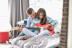 Κόρη διδασκαλίας πατέρων για να παίξει την κιθάρα στο σπίτι στοκ εικόνες με δικαίωμα ελεύθερης χρήσης
